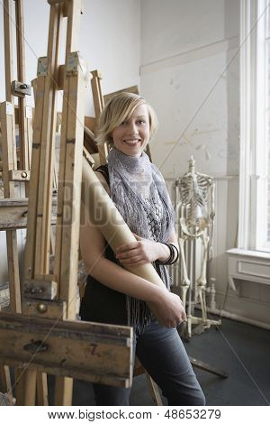 Portrait of a smiling female student standing amid easels in art college