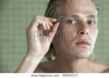 Closeup portrait of handsome young man plucking eyebrows