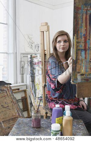Joven artista femenina, pintura de caballete en art studio