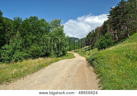 Winding dirt lane, road ascending a mountain