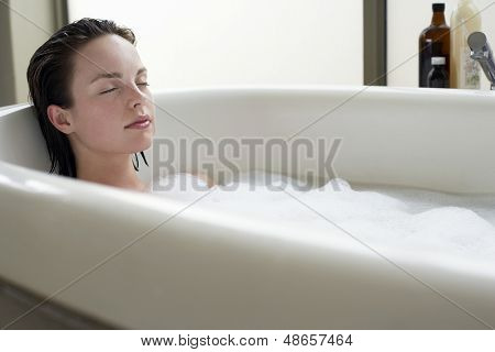 Beautiful young woman relaxing with eyes closed in bathtub