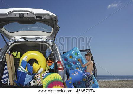 Young boy unloading air mattress from car full of beach accessories