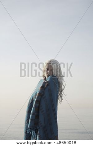 Portrait of beautiful young woman wrapped in blanket standing on beach