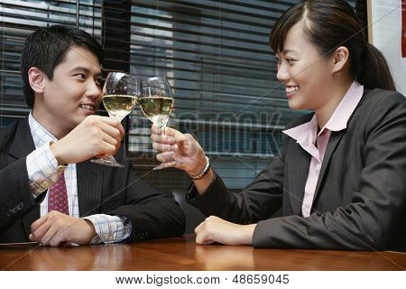 Happy young businessman and businesswoman toasting wineglasses at cafe table