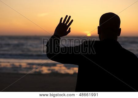 Male Sihouette Waving At Sunset At The Beach