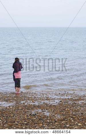 Rear view of young woman wrapped in blanket standing by seaside on beach