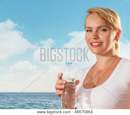 Beautiful Woman Smiling With Water Bottle In Hand On Tropical Beach