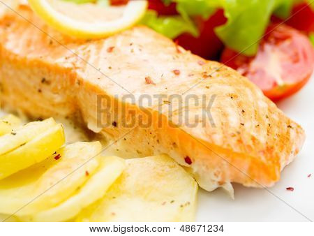 Grilled Salmon, Baked Potatoes With Vegetables Closeup