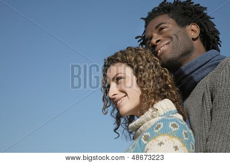 Low angle view of thoughtful young couple looking away against clear blue sky