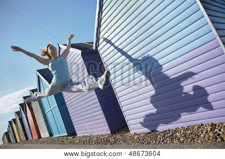 Active young woman jumping in front of beach huts