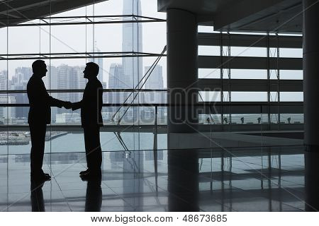 Full length side view of businessmen shaking hands in airport terminal