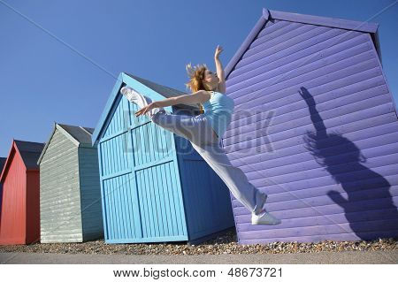 Full length of young woman jumping in front of beach huts against blue sky