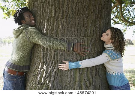 Side view of young multiethnic couple embracing tree trunk at park