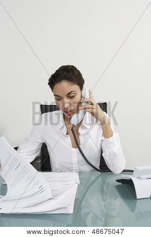 Young businesswoman using landline phone while reading documents at desk in office