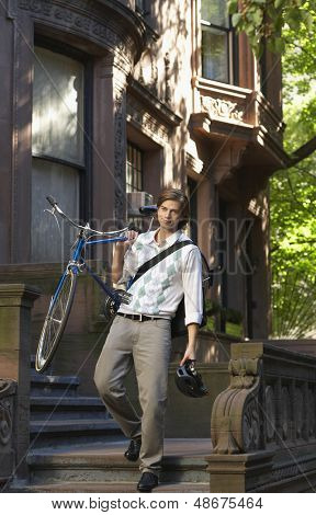 Full length of young businessman carrying bicycle while descending steps
