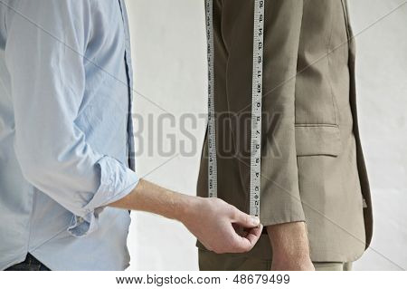 Midsection of young male tailor measuring customer's suit in fashion studio