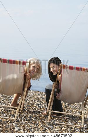 Portrait of happy female friends sitting on deckchairs at beach