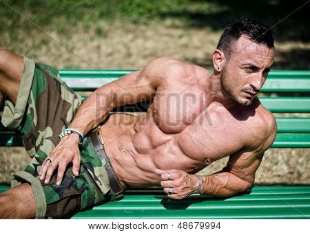 Bodybuilder's Naked Torso, Pecs, Abs, Leaning On A Bench