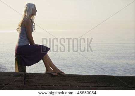 Profile shot of young woman sitting on a wooden bale against sea at beach