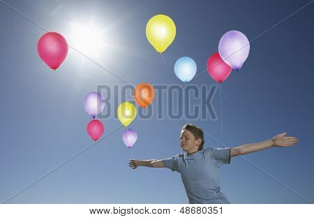 Carefree elementary boy in midair with colorful balloons against blue sky