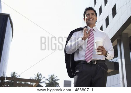 Low angle view of happy young businessman walking with takeaway coffee cup outdoors