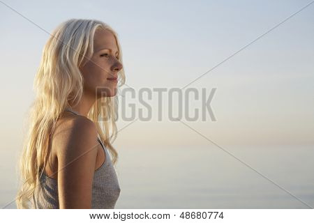 Side view of beautiful young woman standing on beach
