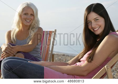 Portrait of beautiful female friends sitting on deckchairs at beach