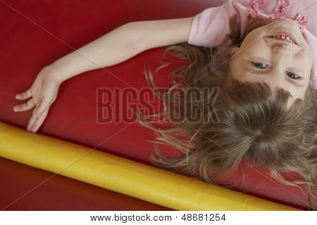 Portrait of cheerful little girl lying in bouncy castle