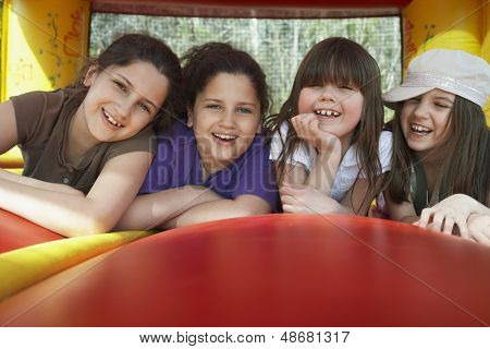 Portrait of cheerful young girls lying in bouncy castle