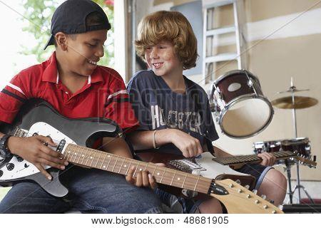 Happy multiethnic boys playing guitars in garage