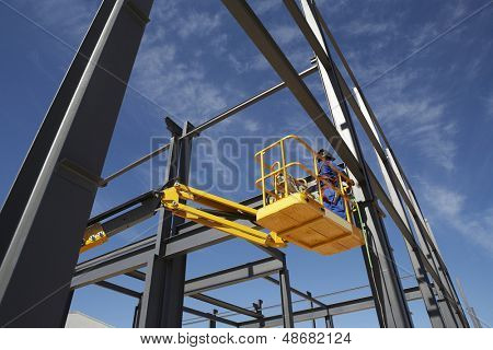 Welder working from cherry picker on steel framing structure