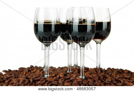 Glasses of liquor and coffee grains, isolated on white