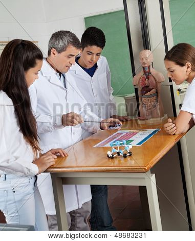 Male teacher teaching experiment to teenage high school students at desk in lab