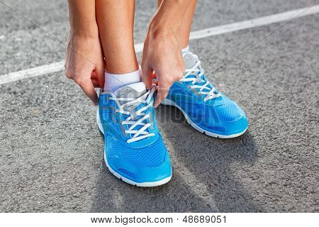 Closeup Of Young Woman Tying Sports Shoe