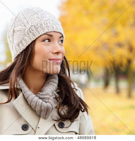Thinking autumn woman looking at fall forest smiling happy walking in colorful autumn foliage outdoors. Happy female model looking thoughtful at copy space outside in beautiful nature. Girl in 20s.