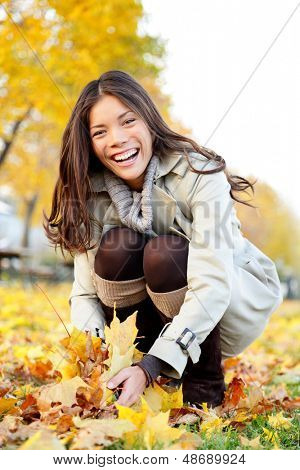 Autumn woman playing with colorful fall leaves in city park smiling happy and excited. Stylish modern brunette close up portrait of mixed ethnic Chinese Asian / Caucasian female model in her 20s.