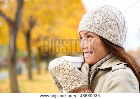Coffee drinking woman in Autumn fall enjoying fall and hot drink from disposable cup. Smiling happy Asian female model in fall foliage. Mixed race Asian Chinese / Caucasian girl in her 20s.