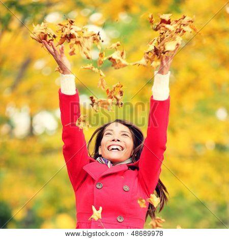 Outono / queda mulher feliz jogando folhas no ar com os braços levantados acima em direção ao céu com smi