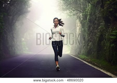 Woman running on road. Female runner jogging on mountain road training for marathon. Fit girl fitness athlete model exercising outdoor.