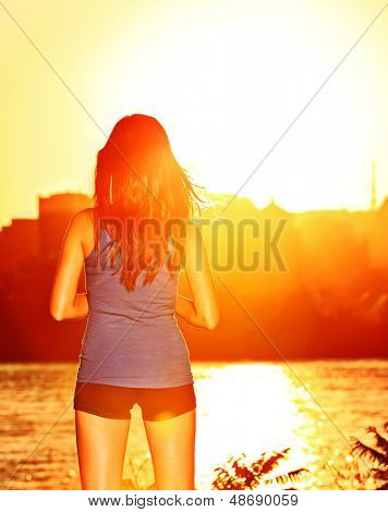 Woman enjoying sunset sunshine after running and training outdoor. Sporty girl enjoying beautiful sunny sunshine relaxing outside after workout.
