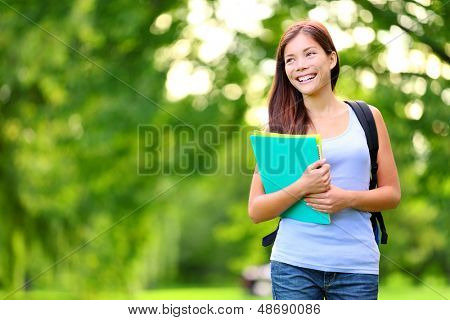 Student girl outdoor in park smiling happy going back to school. Asian female college or university student. Mixed race Asian / Caucasian young woman model wearing school bag holding books.