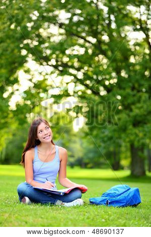 Student girl thinking looking in campus park going back to school at university college. Happy female student sitting studying, writing and reading. Mixed race Asian / Caucasian female student woman