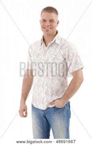 Handsome young man standing in summer shirt, laughing, hand in pocket, isolated on white.