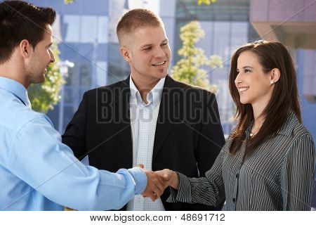 Businesspeople introducing outside of office, shaking hand, smiling.