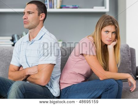 Couple sitting back to back after a fight on the couch with woman looking at camera in sitting room at home