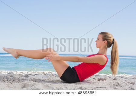 Fit blonde doing pilates core exercise on the beach