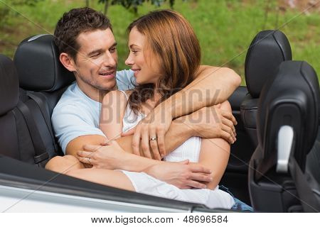 Couple in love cuddling in the backseat of convertible