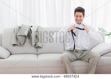 Smiling businessman sitting on sofa loosening his tie at home after long day
