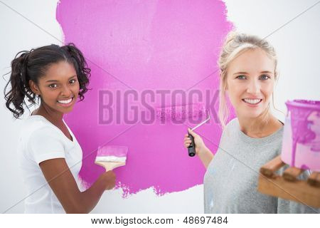 Smiling housemates painting wall pink and looking at camera in new home