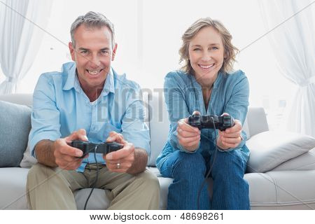 Happy couple playing video games together on the couch at home in the living room